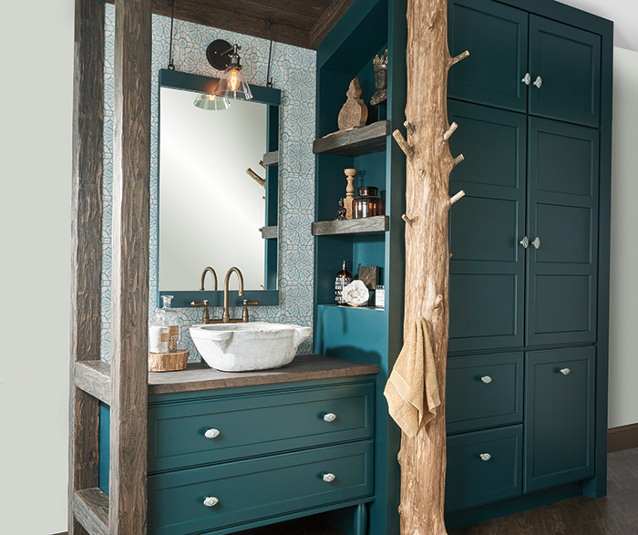 Teal green bathroom vanity and storage cabinets with a tree trunk towel rack